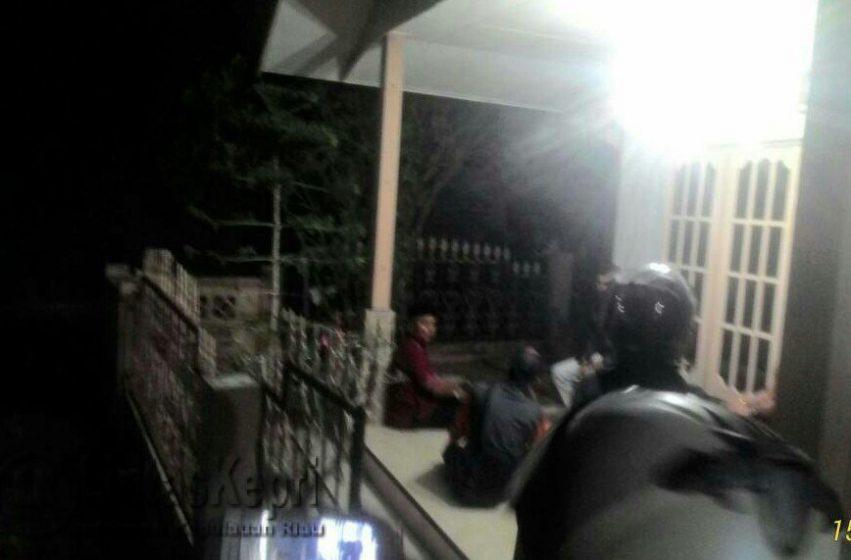 AG terlihat duduk di teras rumah wanita bersuami saat digrebek istrinya, Kamis (15/6).