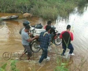 Pengguna jalan memikul kendaraannya melintasi sungai.