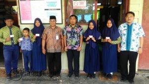 Kadisduk Natuna Ilham Kauli, Kabid Pendaftaran, Trisulo dan Kepsek SMPN 001 Bunguran Tengah, Warriyanto, saat berfoto bersama siswa-siswi penerima KIA.