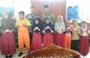 Foto bersama Kepsek SDN 001 Harapan Jaya, Burhaji dan siswa-siswi penerima KIA.