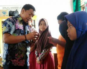 Ilham Kauli menerangkan penggunaan KIA kepada siswa-siswi SDN 001 Harapan Jaya.