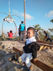 Tampak seorang anak pengunjung sedang duduk di puncak Gunung Gundul.