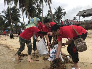 Karyawan Telkomsel tampak sedang membersihkan pantai, dalam rangka Bakti Sosial.