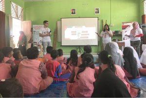 Karyawan Telkomsel sedang memberikan edukasi kepada siswa-siswi sekolah, terkait InternetBAIK.