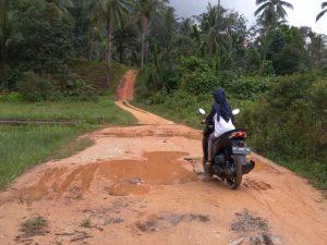 Salah seorang pengguna jalan tampak kesulitan saat melintasi Gang Bulan yang tergenang air saat hujan.