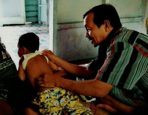 Nazir tampak sibuk mengurut seorang balita yang menjadi pasiennya.