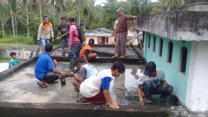 Puluhan warga Sebintang tampak sibuk membersihkan atap Surau Nurhag.