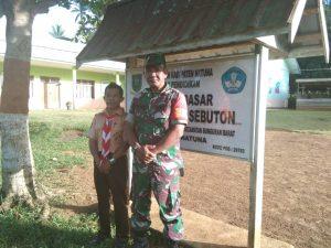 Babinsa Mekar Jaya Serda A. Tanjung foto bersama salah seorang siswa didiknya.