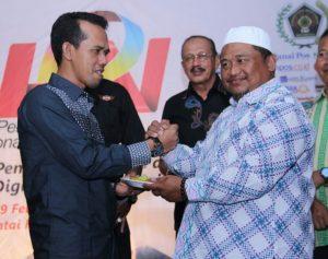Ketua DPRD Natuna Yusripandi saat menerima nasi tumpeng dari perwakilan Insan Pers.