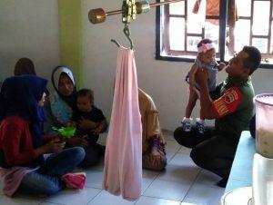 Kopda Sawaliadi tampak sedang membantu petugas untuk menimbang bayi.