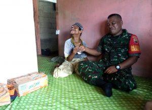 Babinsa Semedang Saifullah Torang, saat bersenda gurau dengan saudara Toyib, sambil memberikan bantuan.