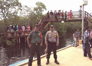 Serda Azhar Tanjung dan Brigadir Moris Tua saat mendampingi rombongan wisatawan luar negeri menikmati pemandangan wisata hutan mangrove di Desa Mekar Jaya.