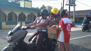 Tampak salah seorang anggota FKPS Natuna, sedang menyodorkan kardus kepada aparat Kepolisian, yang hendak menyumbang dana.