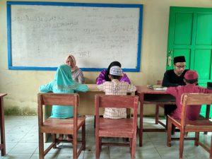 Moh. Zahirul Alim (pria berkacamata) saat mengajar aksara kepada sejumlah anak didiknya.