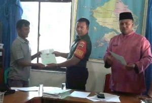 Sertu Budihardjo tampak ikut menyerahkan sertifikat tanah kepada salah seorang warga penerima.
