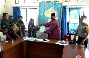 Kades Kelarik Utara, Zapridin, saat menyerahkan sertifikat tanah untuk warganya.