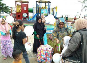 Tampak Kasi Partisipasi Anak Dinsos PPPA Natuna, Riyana Juliati, saat membagikan balon dan bingkisan snack kepada salah seorang anak yang sedang berkunjung di Taman Bermain Anak Luar Ruangan di Pantai Kencana Ranai.