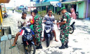 Para anggota TNI AD dari jajaran Koramil 03/Sedanau, saat membagikan bendera.