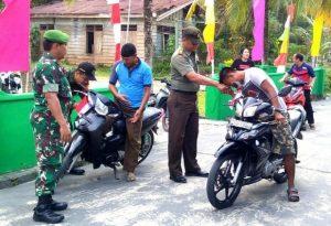 Danramil 03/Sedanau Kapten (Arm) Bambang Hendratno, beserta jajarannya saat memnagikan bendera kepada pengendara.
