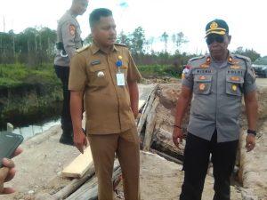 Tampak Wakapolres Natuna Kompol Wisnu bersama Camat Bunguran Utara Mardi Hendrika, saat meninjau lokasi jembatan ambruk disungai Semala.