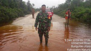 Babinsa Kelarik Utara Sertu Budihardjo, saat ikut meninjau jalan banjir diantara Kecamatan Bunguran Utara dan Kecamatan Bunguran Utara.
