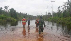 Sertu Budihardjo bersama Anggota DPRD Natuna, Camat Bunguran Utara dan Kades Kelarik Utara, saat meninjau air yang menggenang di jalan poros antara Batubi dan Kelarik, Kabupaten Natuna.