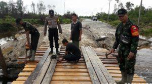 Tampak Anggota TNI, POLRI dan Masyarakat sedang melaksanakan Goro melanjutkan perbaikan jembatan yang putus diterjang banjir.