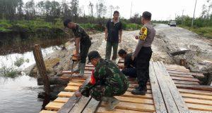 Babinsa, Bhabinkamtibmas dan Warga Kelarik saat memperbaiki jembatan di A Sungai Semala.